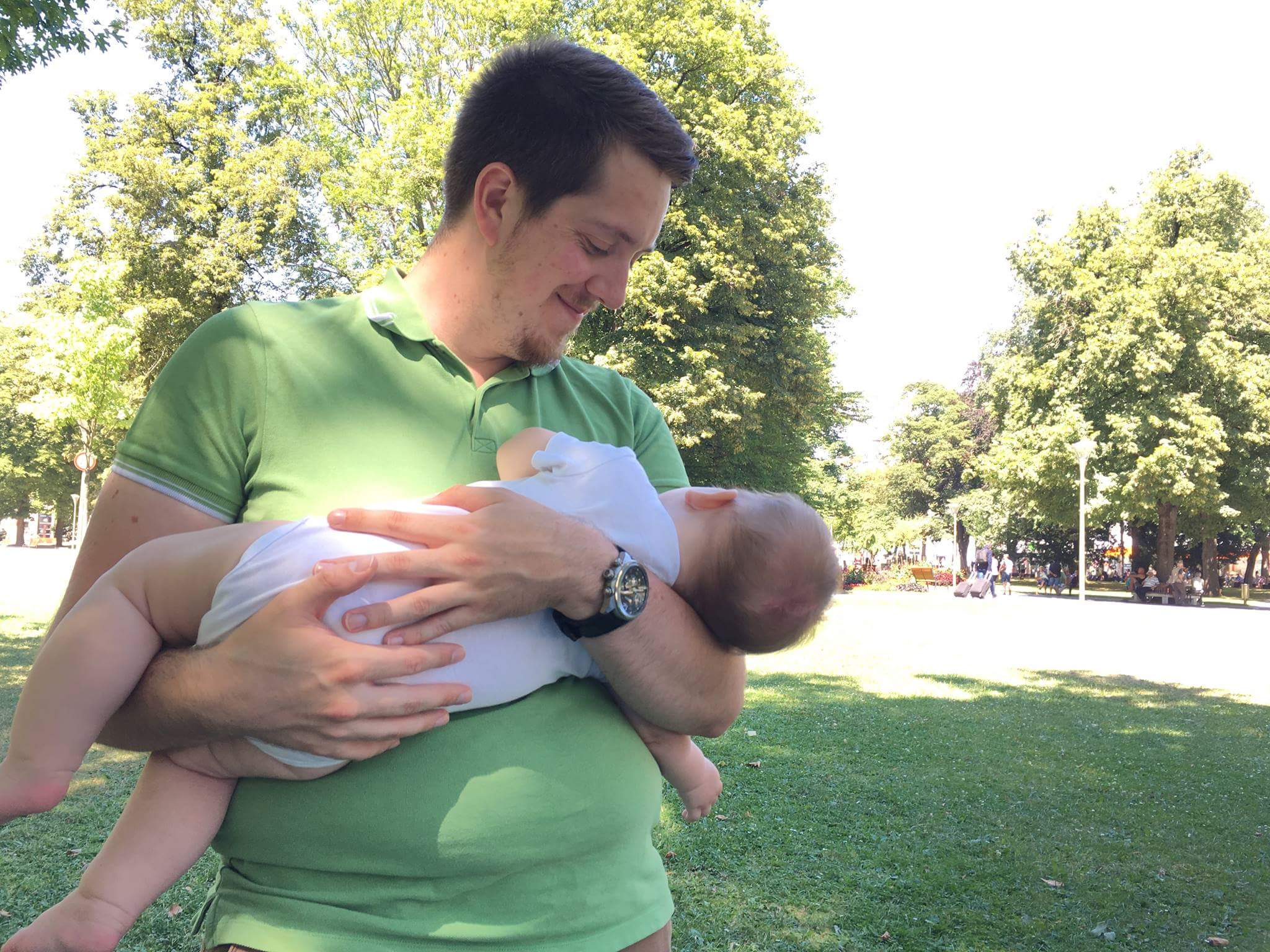 Vater hält Baby zum Schlafen in der Wiege