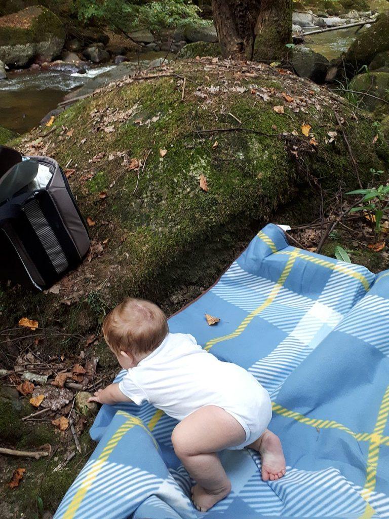 Baby krabbelt auf Picknickdecke im Aisttal