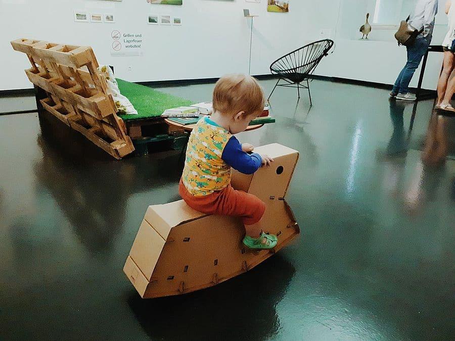 Unser Sohn auf dem Karton Schaukelpferd in der Ausstellung Stadtoasen im NORDICO Stadtmuseum in Linz